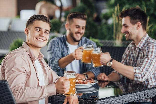 Прекрасный день, три бизнесмена сидят на летней террасе в кафе и пьют пиво.