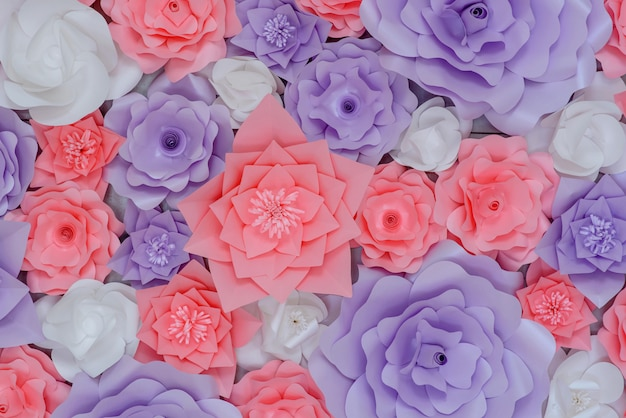 Beautiful decor of colored pink and purple paper flowers on the wall
