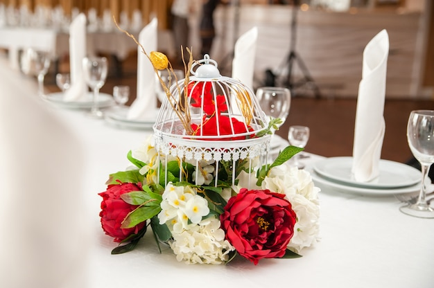 Beautiful decor of flowers on the festive table. cage.