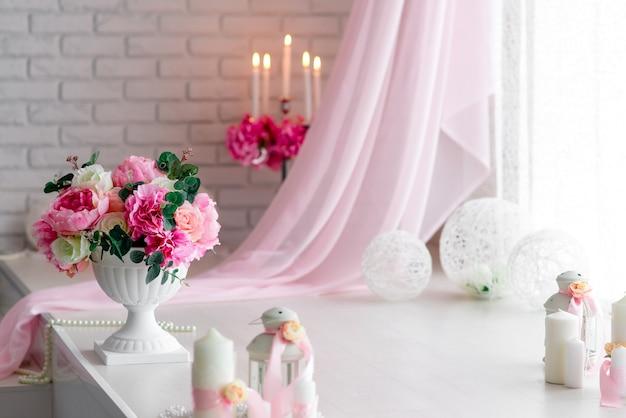 양초와 꽃의 아름다운 장식. 화이트 핑크 음영.