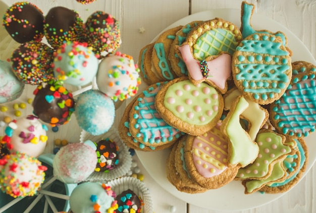 Beautiful decorated cake pops and cookies for easter on table