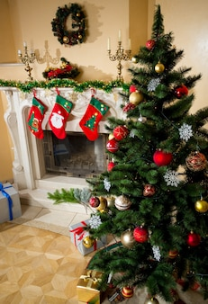 Beautiful decorated christmas tree next to fireplace with stockings for gifts at living room