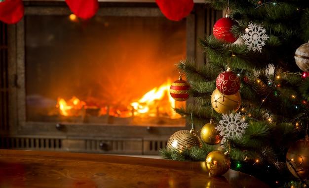 천연 통나무가 있는 불타는 벽난로 옆에 아름답게 장식된 크리스마스 트리