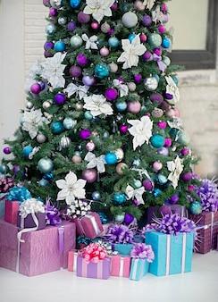 Красиво украшенная елка под ней - подарки основные цвета игрушки белый фиолетовый