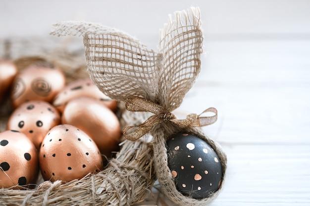 Красиво оформленные пасхальные яйца золотистого цвета с черными точками и одно черное яйцо с золотыми точками