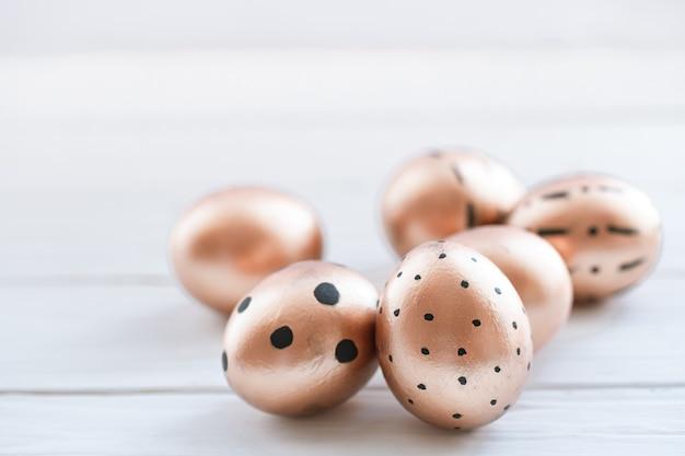 Красиво оформленные пасхальные яйца золотистого цвета с черными точками
