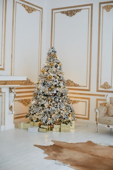 Beautiful decorated golden christmas tree with present boxes under it in vintage luxurious interior decorated for new year.