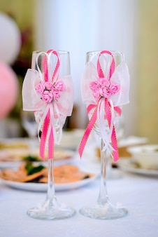 ピンクのリボンで美しく飾られた結婚式のメガネ