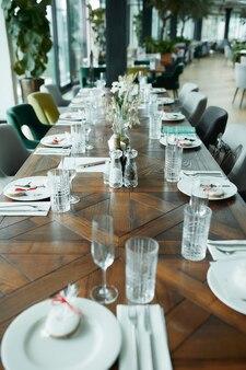 Красивое украшение праздничного стола посудой и столовыми приборами, украшенное цветами и лентами. сервировка праздничного стола.