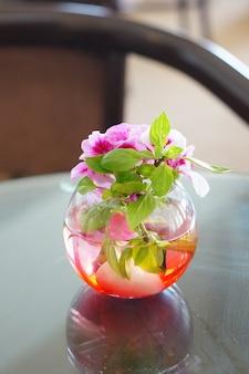 Красивое украшение из розовых цветов в стеклянной вазе на столе в комнате