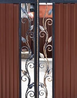 美しい装飾的な金属要素は錬鉄製の門を鍛造しました。