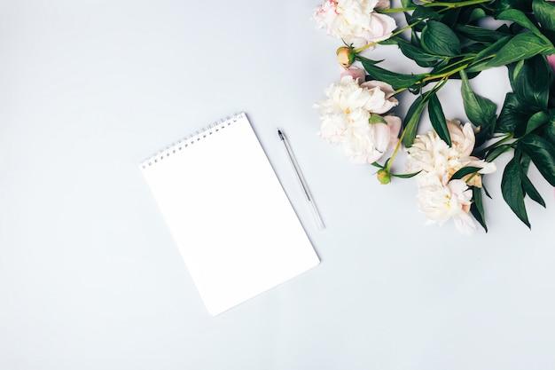 Красивые нежные пионы и блокнот с ручкой на белой поверхности