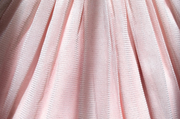 Beautiful delicate pink background. shiny mesh fluffy fabric close-up text