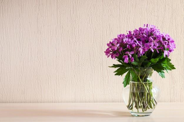 コピー スペース付きのテーブルの上のガラスの花瓶に美しい繊細な紫の野の花 ミニマルな家の装飾