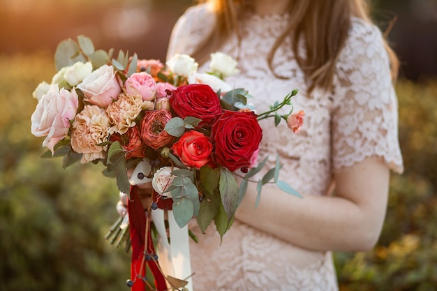 Beautiful delicate wedding bouquet in the hands of the bride