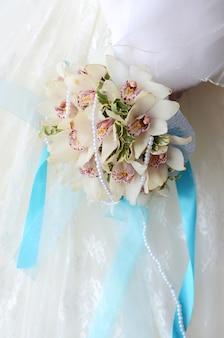 花嫁の手に白とベージュの花の美しい繊細なウェディングブーケがクローズアップ