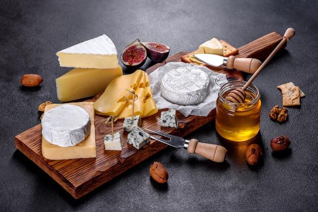 Красивый вкусный сыр камамбер, пармезан, бри с виноградом и инжиром на деревянной доске. закуски к вину на празднике
