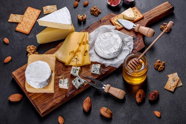 Красивый вкусный сыр камамбер, пармезан, бри с виноградом и инжиром на деревянной доске. закуски к вину