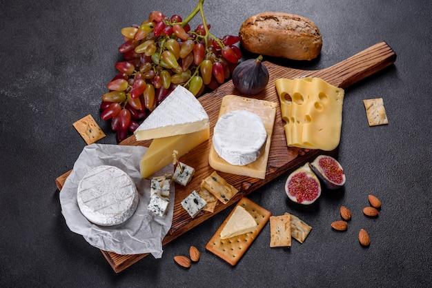 Красивый вкусный сыр камамбер, пармезан, бри с виноградом и инжиром на деревянной доске.