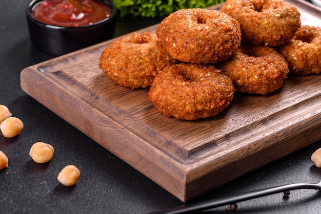 Beautiful delicious fresh chickpea falafel with sauces on a concrete background. elements of vegitarian cuisine