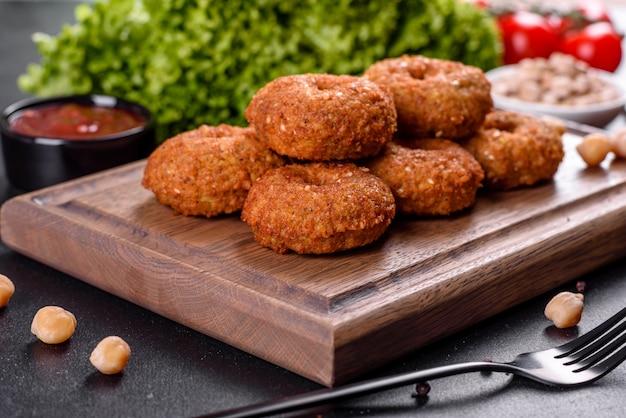 コンクリートのテーブルの上にソースと美しいおいしい新鮮なひよこ豆のファラフェル。ベジタリアン料理の要素