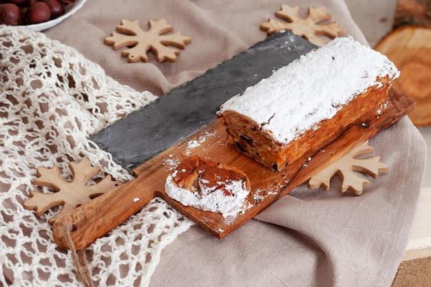 축제 시즌을 축하하기위한 장식 항목과 나무 보드에 아름다운 맛있는 수제 크리스마스 말린 과일 케이크
