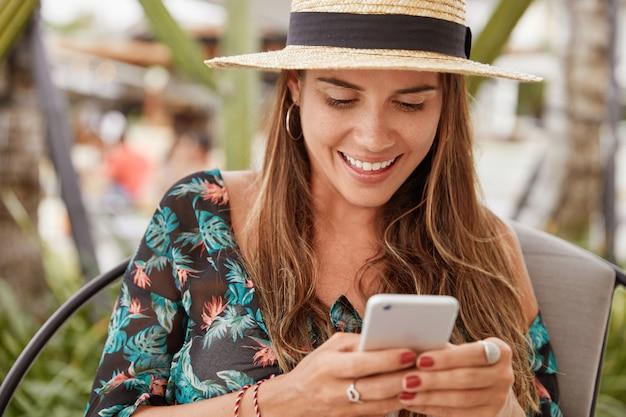 美しい喜びの女性観光客はエキゾチックな国にかかって、夏の麦わら帽子とブラウスを着て、居心地の良いカフェテリアで無線インターネットに接続された携帯電話でメッセージを入力します。人と休暇