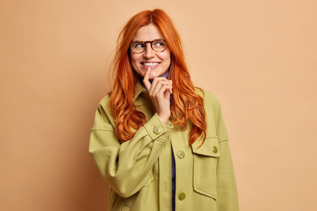 Beautiful delighted red haired young woman looks with dreamy satisfied expression keeps index finger on lips dressed in stylish green jacket has good idea in mind.