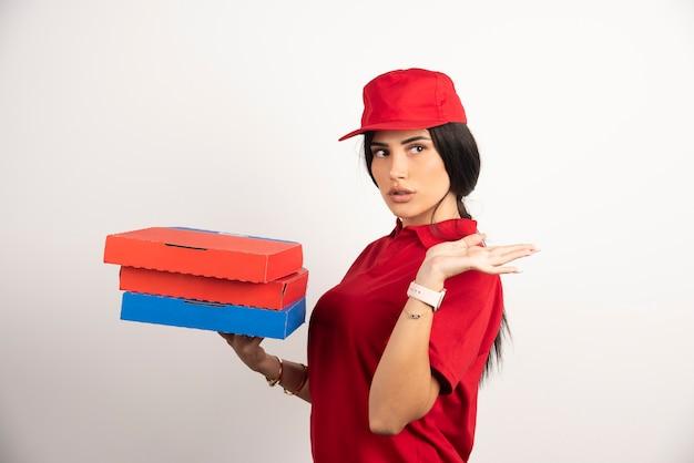 Bella donna di consegna che tiene mazzo di scatole per pizza.