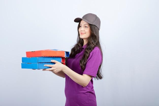Bella donna delle consegne in uniforme viola che dà scatole per pizza. foto di alta qualità