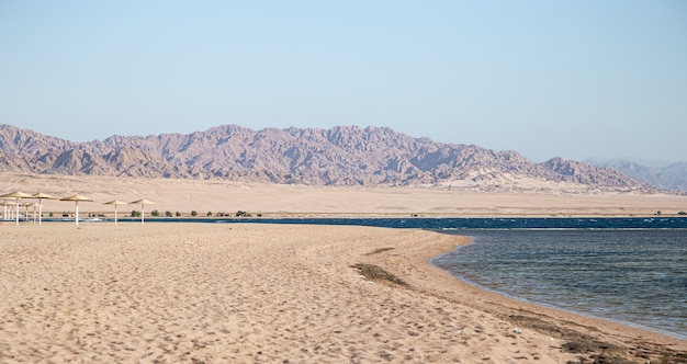 Beautiful deserted sandy beach against the mountains.