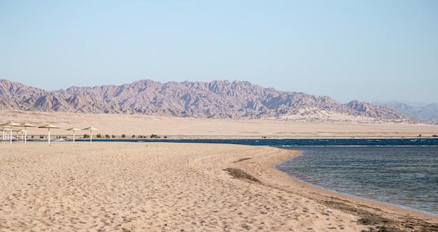 Красивый пустынный песчаный пляж на фоне гор.