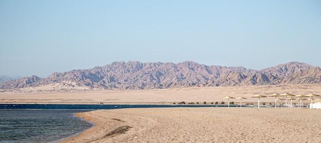 산의 배경에 아름 다운 황량한 모래 해변. 야생 관광 및 여행 개념.