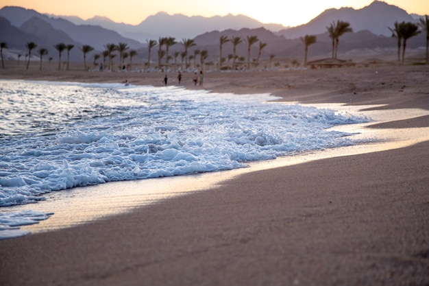 Beautiful deserted sandy beach at sunset with sea waves against the background of mountains.