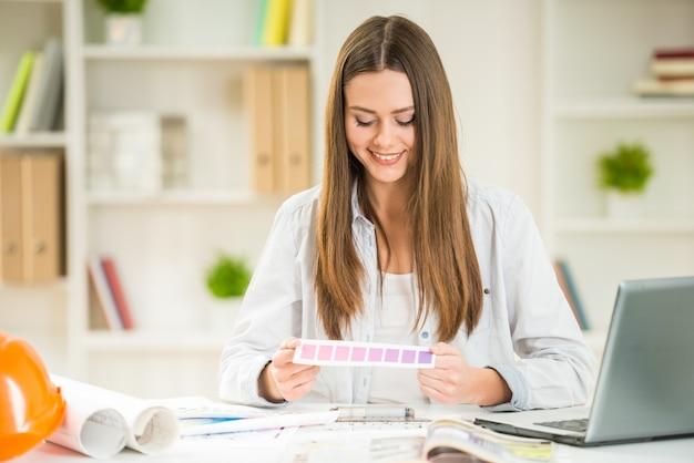 Прекрасный дизайнер работает с образцами цветов в своем кабинете.