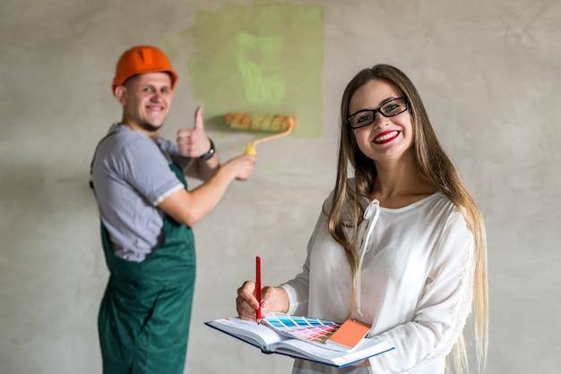 労働者が壁を塗っている間、メモ帳で書く美しいデザイナー