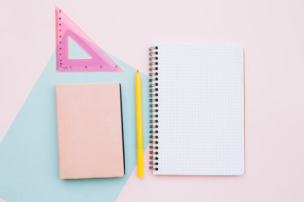 Beautiful desktop with notebook and ruler on pink background