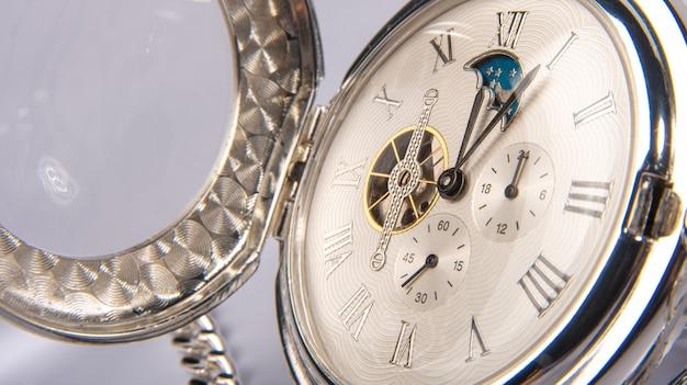 Красивые детали старых карманных часов на белой поверхности