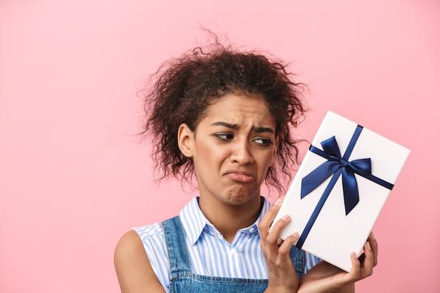 Красивая разочарованная молодая африканская женщина, держащая подарочную коробку над розовым