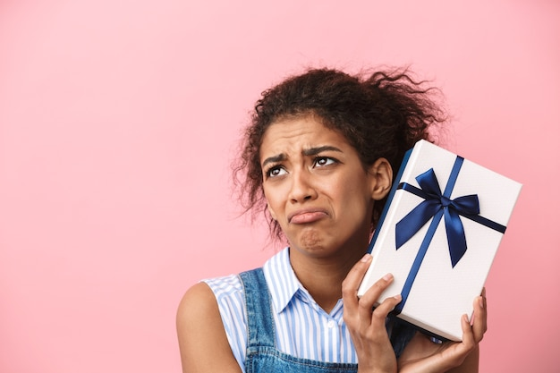 Beautiful disappointed young african woman holding gift box over pink