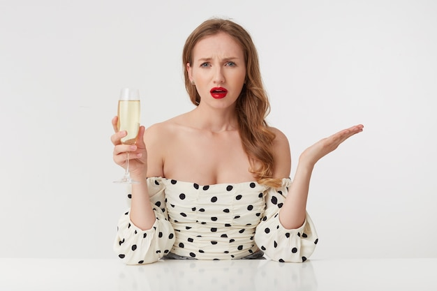 Beautiful disappointed young lady with long blond hair, with red lips in a polka-dot dress, raising a glass of champagne, wants to ask a question looking at camera isolated over pink background.