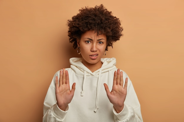 美しい不満のミレニアル世代の女性は、カメラに向かって手を引っ張る、停止ジェスチャーまたは警告サインを作る、白いパーカーを着ています
