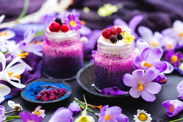 Прекрасная демонстрация фиолетовых весенних веганских смузи, украшенных яркими цветами