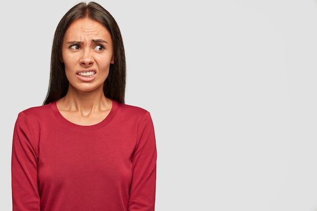 La bella donna dispiaciuta aggrotta le sopracciglia con dispiacere e avversione