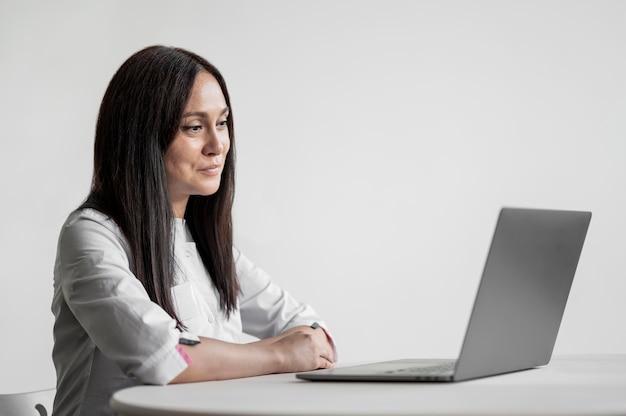 Beautiful doctor browsing laptop