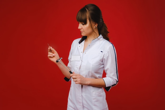 A beautiful doctor girl holds a reflex hammer and smiles at the camera isolated on a red background.