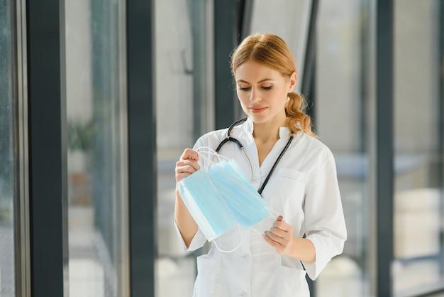 Красивый доктор, держащий в руке защитную маску, рад закончить карантин. копия пространства, белый фон.
