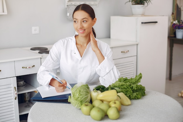 Beautiful doctor in a kitchen with vegetables