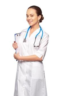 白い背景に立っている美しい医者。スタジオショット。