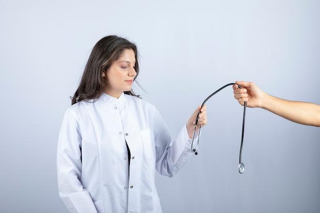 Bello medico in camice bianco che cattura lo stetoscopio da un'altra persona.